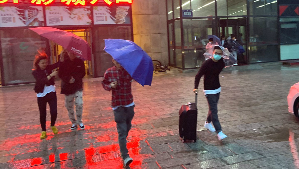 """台风""""美莎克""""过境 长春街头行人在大风大雨中艰难前行"""