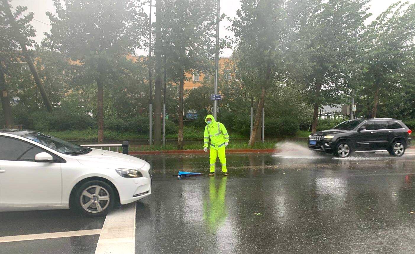 大雨滂沱,交警雨中执勤,过往车辆为交警送伞